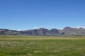 Island - weite Landschaft, grüne Wiesen, Berge